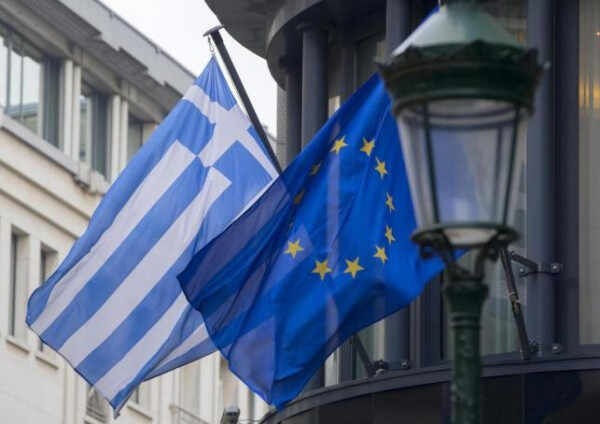 A Greek and a European flag flutter outside the Greek embassy in Brussels