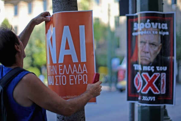 ATHENS, GREECE - JULY 03:  A man erects a Nai (yes) poster next to a rival Oxi (no) poster as electioneering on the referendum continues on July 3, 2015 in Athens, Greece. The 'Yes' and 'No' supporters  in Greece are set to hold major rallies in Athens today ahead of Sunday's referendum on an international bailout terms.  (Photo by Christopher Furlong/Getty Images)