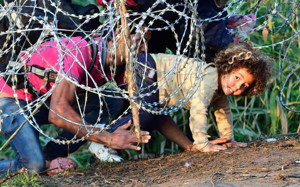 "TOPSHOTS Migrants crawl under a barbed fence at the Hungarian-Serbian border near Roszke, on August 27, 2015. As Europe struggles with its worst migrant crisis since World War II, Hungary has become, like Italy and Greece, a ""frontline"" state. So far this year, police say around 141,500 migrants have been intercepted crossing into Hungary, mostly from neighbouring Serbia.  AFP PHOTO / ATTILA KISBENEDEKATTILA KISBENEDEK/AFP/Getty Images"