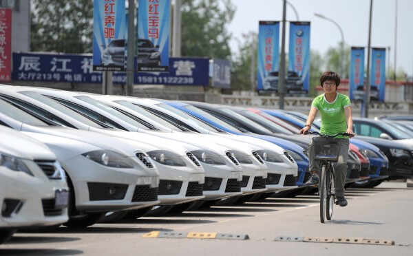 A woman rides a bicycle past a row of new cars for sale at a car market in Bejing on May 16, 2012. A slew of bleak data has raised fears China's economy is cooling faster than previously thought, but analysts say Beijing has only limited means to prevent a politically damaging slowdown. AFP PHOTO / LIU JIN        (Photo credit should read LIU JIN/AFP/GettyImages)