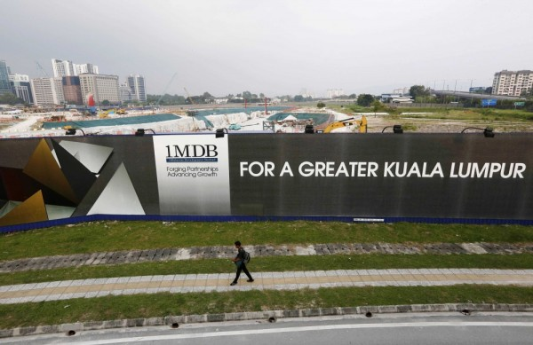 A man walks past a 1 Malaysia Development Berhad (1MDB) billboard at the funds flagship Tun Razak Exchange development in Kuala Lumpur, in this March 1, 2015 file photo. Malaysia's indebted and controversy-ridden state investor 1MDB will be left as a skeletal structure and possibly dissolved under a debt repayment plan in which most of its assets will be sold, sources with direct knowledge of the matter said. REUTERS/Olivia Harris/Files (MALAYSIA - Tags: BUSINESS LOGO REAL ESTATE)